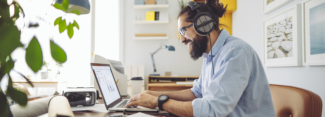 man with headphones sitting at laptop